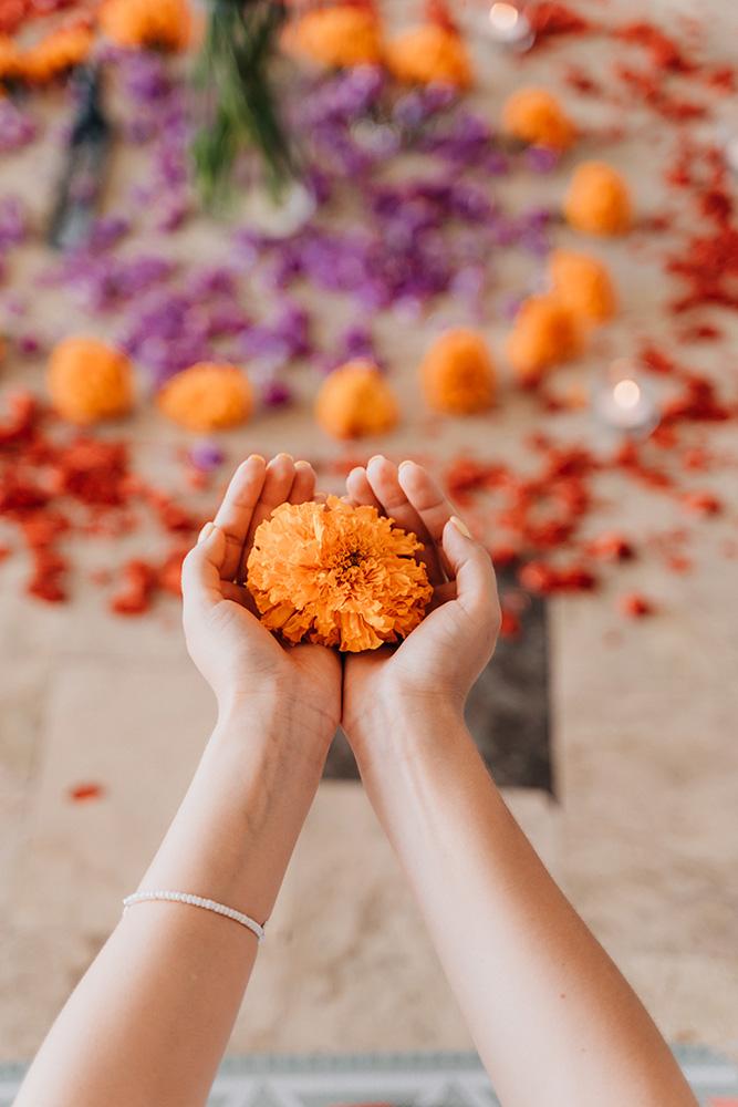 Femme tenant dans ses mains une fleur de souci.